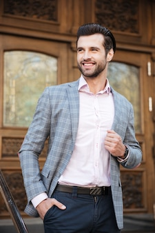 Portrait of a smiling man in jacket posing outdoors