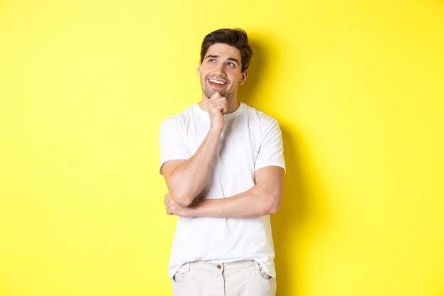 Portrait of smiling man looking thoughtful at upper left corner, choosing something, have an idea, standing against yellow background.
