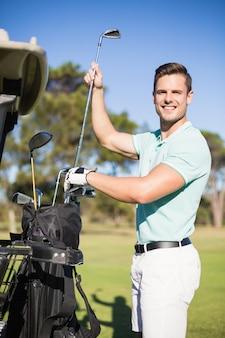 Portrait of smiling man putting golf club in bag