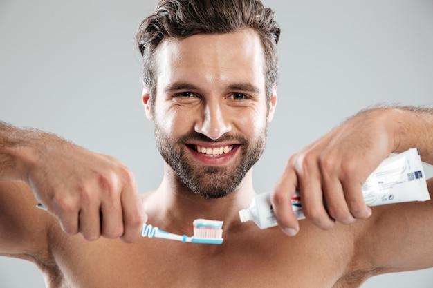 Ritratto di un uomo sorridente che mette dentifricio in pasta su uno spazzolino da denti