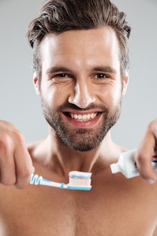 Portrait of a smiling man putting toothpaste on a toothbrush