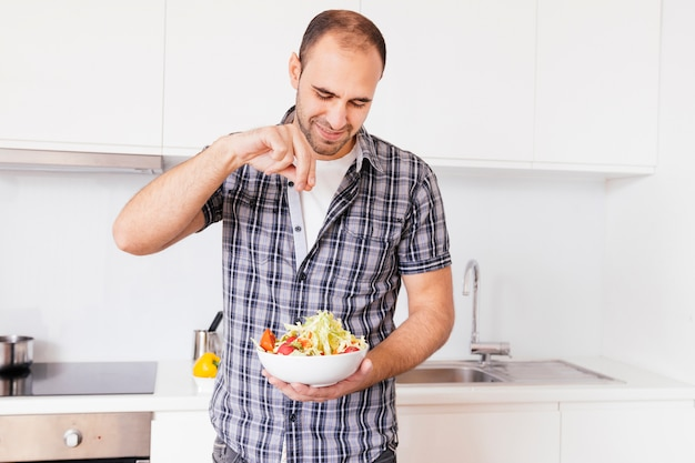 Portrait of a smiling man seasoning the salt on salad in the kitchen