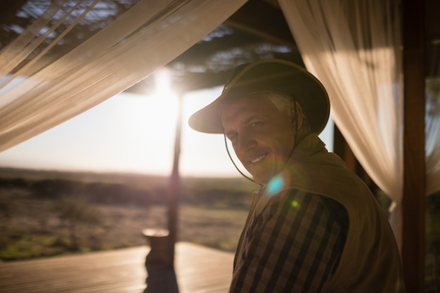 Portrait of smiling man sitting on canopy bed