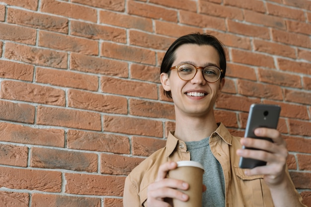 Portrait of smiling man in stylish eyeglasses using cellphone, holding cup of coffee