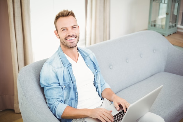 Portrait of smiling man using laptop at home