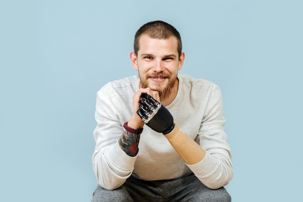 Portrait of a smiling man with artificial hand in casual clothes