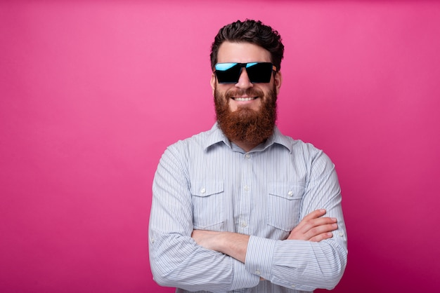 Portrait of smiling man with beard wearing sunglasses and standing over pink background with crossed arms