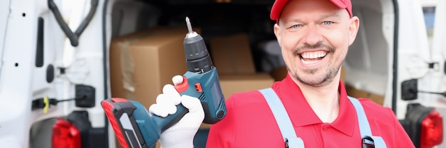 Portrait of smiling man with drill in his hands