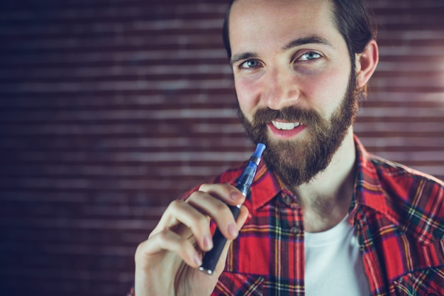 Portrait of smiling man with electronic cigarette