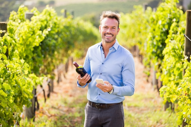 Portrait of smiling man with wine bottle using phone