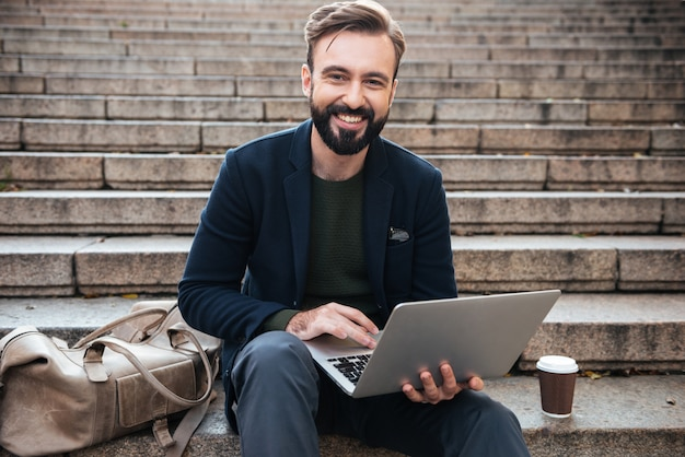 Portrait of a smiling man working on laptop