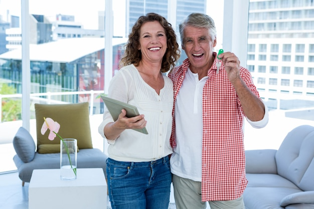 Portrait of smiling mature couple with tablet and house key