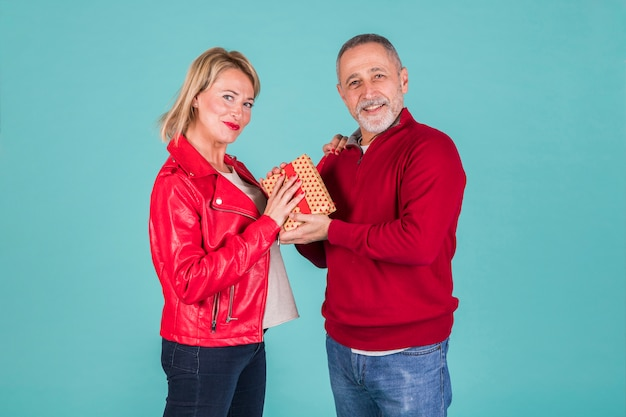Portrait of smiling mature man giving present to his wife in red jacket