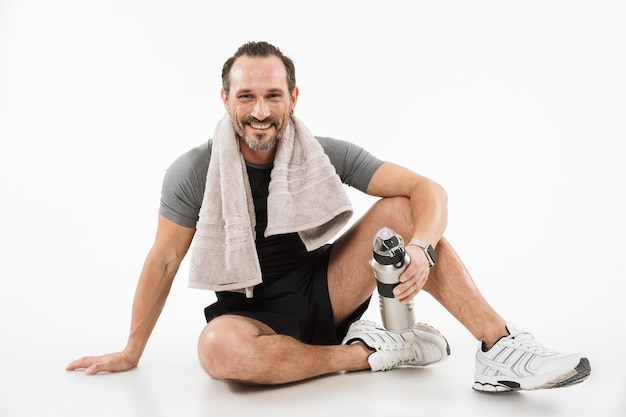 Portrait of a smiling mature sportsman drinking water