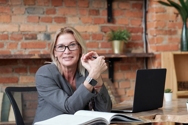 Portrait of smiling mature woman in glasses sitting at desk with laptop in loft office and examining notes in accounting book