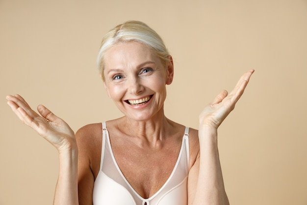 Portrait of smiling mature woman with blonde hair in white underwear looking at camera throwing up
