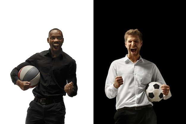 Portrait of a smiling men holding soccer and basketball ball isolated on a white and black background. the success happy afro and caucasian men. mixed couple.