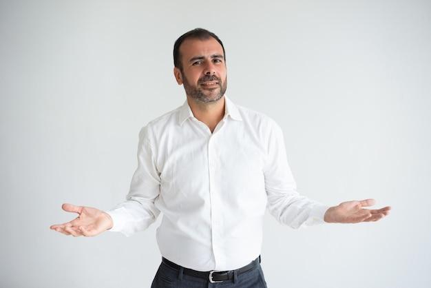 Portrait of smiling mid adult businessman shrugging shoulders.
