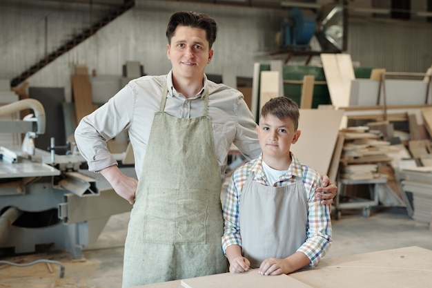 Portrait of smiling middle-aged carpenter in apron embracing teenage son in furniture workshop
