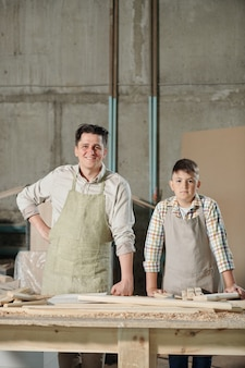 Portrait of smiling middle-aged carpenter and his teenage son in aprons standing at table with wooden pieces in workshop
