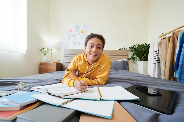 Portrait of smiling mixed race high school girl lying on bed among workbooks in own room and taking notes while doing homework