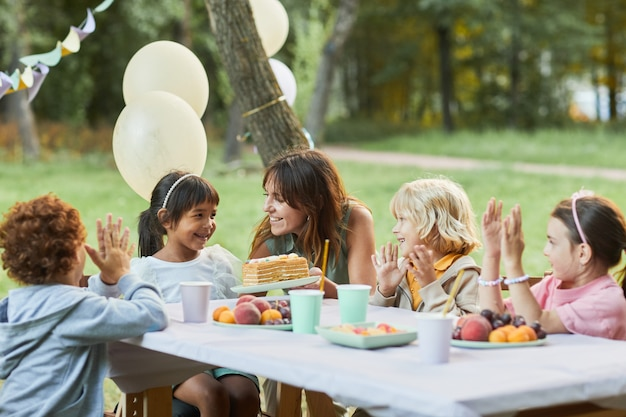 Portrait of smiling mother bringing birthday cake to cute girl during birthday party outdoors copy s...
