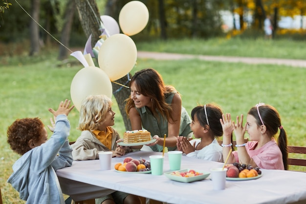 Portrait of smiling mother bringing birthday cake to little boy during birthday party outdoors copy ...