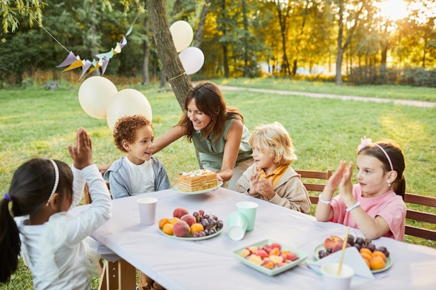 Portrait of smiling mother bringing birthday cake to son during birthday party outdoors in sunlight