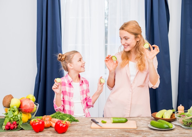 Portrait of a smiling mother and daughter holding cucumber slice in hand looking at each other
