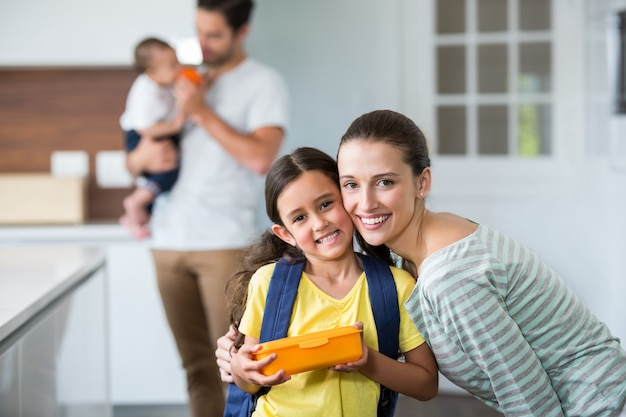 Portrait of smiling mother and daughter holding lunch box