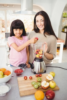 Portrait of smiling mother and daughter preparing fruit juice