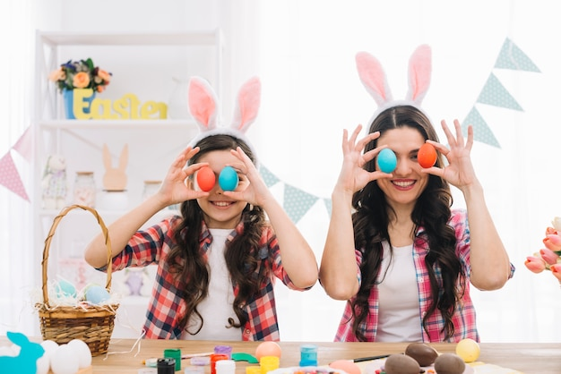 Portrait of smiling mother and her daughter covering their eyes with easter eggs