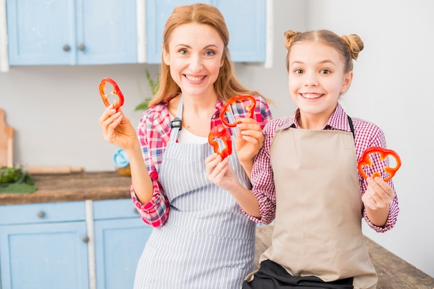 Portrait of smiling mother and her daughter looking at camera holding bell pepper slice in hand