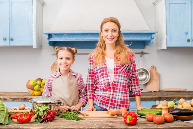Portrait of a smiling mother and her daughter standing in front of table with vegetables