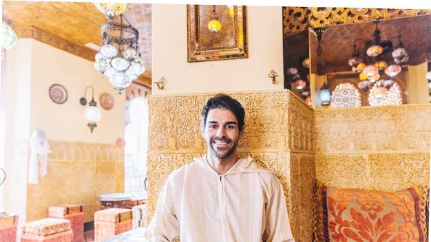 Portrait of smiling muslim man in restaurant
