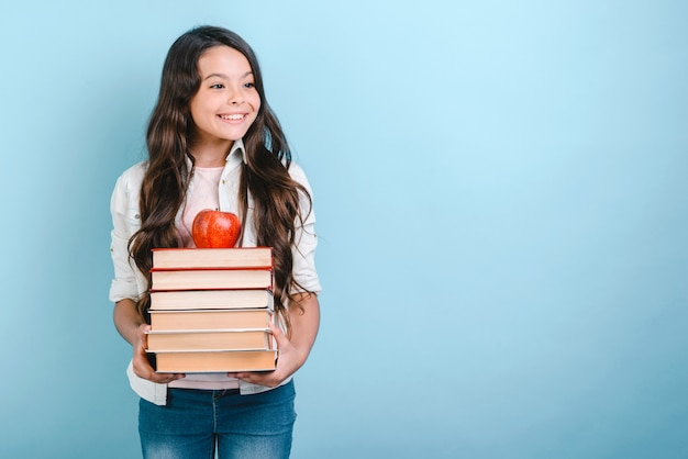 Portrait of smiling nerd young girl holding stack of books with apple on it. back to school.