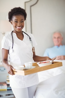 Portrait of smiling nurse with breakfast in tray while senior man lying on bed