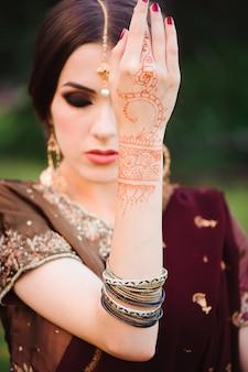 美しいインドの女の子の笑顔の肖像画。赤いジュエリーセットの若いインド人女性モデル。