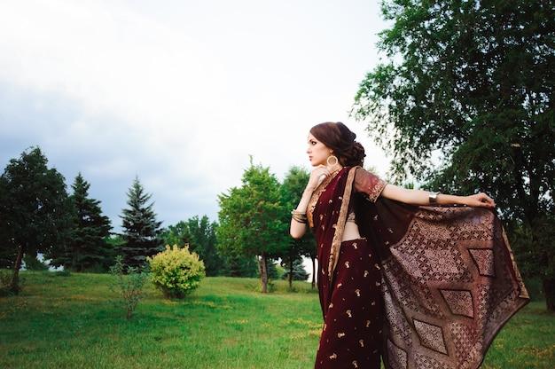 Портрет улыбается красивой индийской девушки. молодая индийская модель женщины с красным комплектом ювелирных изделий.