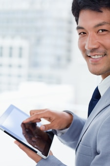 Portrait of a smiling office worker using a tablet computer