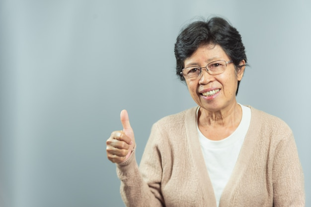 Portrait of smiling old woman on gray