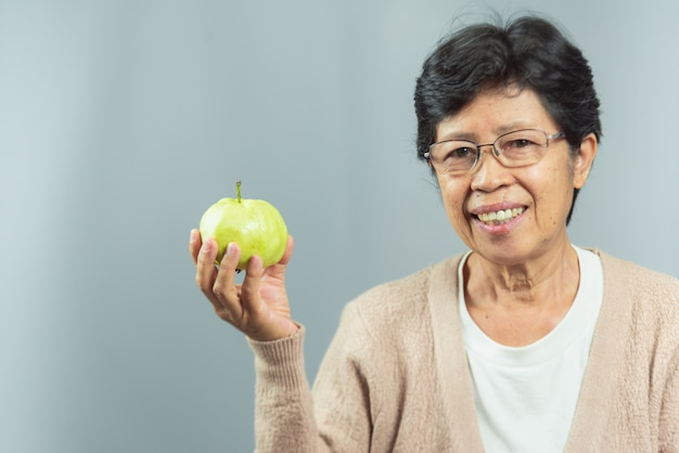 Portrait of smiling old woman holding  green fruit on gray