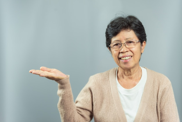 Portrait of smiling old woman showing gesture with hand on gray