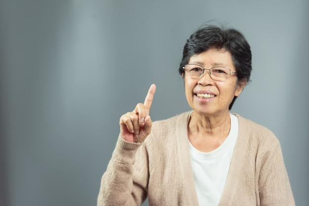 Portrait of smiling old woman thinking ideas on gray