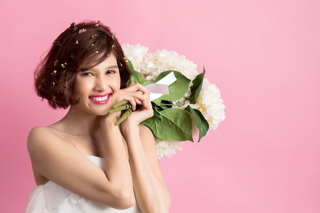 Portrait of a smiling playful cute woman holding flowers isolated on pink