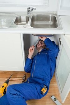 Portrait of a smiling plumber fixing a sink
