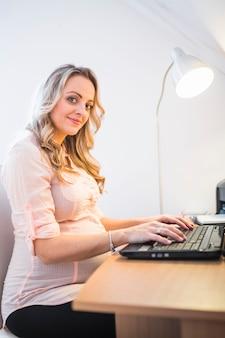 Portrait of a smiling pregnant woman using laptop keypad