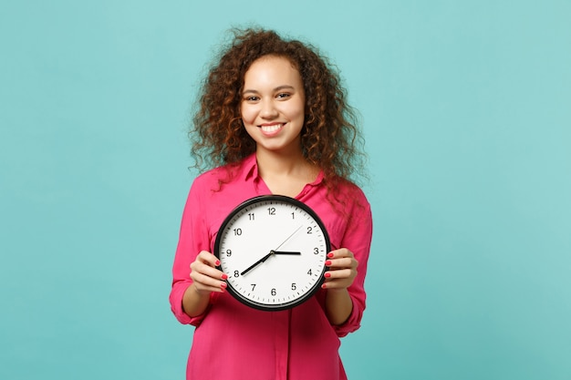 Portrait of smiling pretty african girl in pink casual clothes holding round clock isolated on blue turquoise wall background in studio. people sincere emotions, lifestyle concept. mock up copy space.