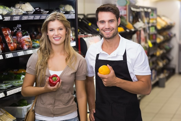 Portrait of smiling pretty blonde woman buying a vegetable at seller