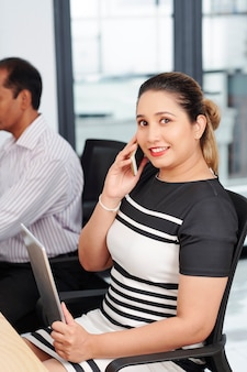 Portrait of smiling pretty business lady with tablet computer in hands sitting at office desk and talking on phone